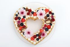 Heart shaped layer cake top view. Heart shaped layer cake decorated with fresh berries, chocolate and flowers. On white background with clipping path. Top view royalty free stock photo