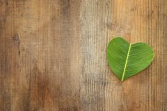 Heart shaped leaf over wooden table. ecology and health concept. Heart shaped leaf over wooden table. ecology and health concept Royalty Free Stock Photography