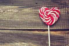 Heart shaped lollipop for Valentine's Day. On the old wooden background. Vintage toned picture Royalty Free Stock Images