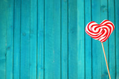 Heart shaped lollipop for Valentine's Day with turquoise backgro Royalty Free Stock Photo