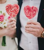 Heart shaped lollipops in hands. Bride and groom holding candy heart Royalty Free Stock Photos