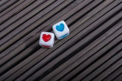 Heart shaped love cubes  on a straw mat. Colorful heart shaped love cubes  on a straw mat Royalty Free Stock Photo