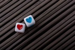 Heart shaped love cubes  on a straw mat. Colorful heart shaped love cubes  on a straw mat Royalty Free Stock Photos