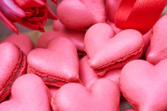 Heart-shaped macarons with flowers and ribbon on a wooden table. Creative decoration for Valentine's Day Stock Photography
