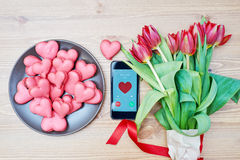 Heart-shaped macarons with flowers and ribbon on a wooden table. Creative decoration for Valentine's Day Stock Images