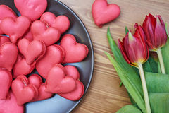 Heart-shaped macarons with flowers and ribbon on a wooden table. Creative decoration for Valentine's Day Royalty Free Stock Photo