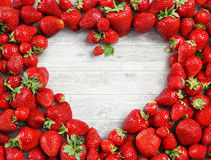 Heart shaped made of strawberry on white wooden background. Stock Photography