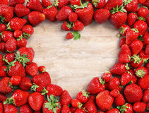 Heart shaped made of strawberry on wooden background. Royalty Free Stock Image