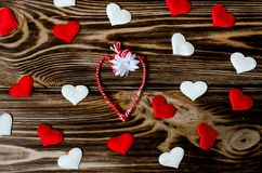 Heart-shaped martisor or martenitsa surrounded by hearts on wooden background stock photos