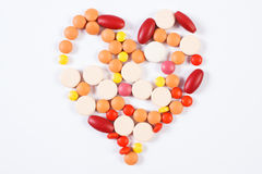 Heart shaped medical pills and capsules on white background, health care concept Royalty Free Stock Photos