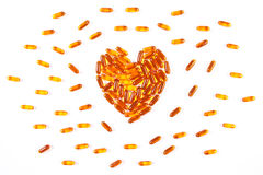 Heart shaped medical pills and capsules on white background, health care concept. Heart shaped orange medical pills, capsules or supplements for therapy on white royalty free stock photo
