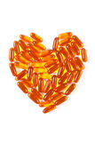 Heart shaped medical pills and capsules on white background, health care concept. Heart shaped orange medical pills, capsules or supplements for therapy on white Stock Photos