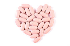 Heart shaped medical pills and capsules on white background, health care concept Stock Photos