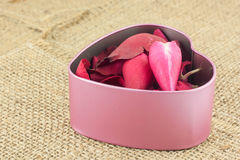 Heart shaped metal box put inside with red rose petals sent to t Stock Photos