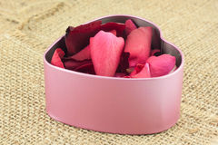 Heart shaped metal box on sackcloth. Heart shaped metal box put inside with red rose petals sent to the sweetheart on sackcloth Royalty Free Stock Images