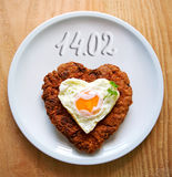 Heart shaped minced steak with fried egg . Stock Photo
