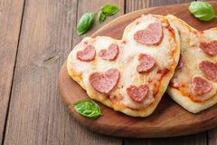 Heart shaped mini pizza with pepperoni. Valentines day menu royalty free stock image