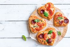 Heart shaped mini pizzas. Over wooden background with copy space. Mini pizzas with tomatoes, pepperoni, mozzarella cheese and basil for Valentine`s day, love Royalty Free Stock Images