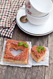 Heart  shaped  napoleon cake with mint on old wooden table Royalty Free Stock Photo