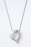 Heart-shaped necklace. Necklace with a heart-shaped pendant decorated with many diamonds Royalty Free Stock Photo