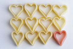 Heart shaped noodles - herzfoermige Nudeln. Many yellow and one red heartshaped noodle - viele gelbe und eine rote herzfoermige Nudel Royalty Free Stock Photography