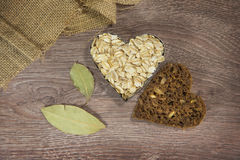 Heart shaped oats and bread. On wood background stock image