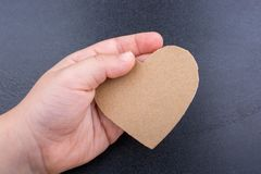 Heart shaped object in hand on a black background Royalty Free Stock Image