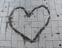 Heart- shaped oil stain on a sidewalk. Heart- shaped oil stain on a brick sidewalk Royalty Free Stock Image