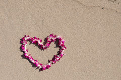 Heart shaped orchid flower garland white sand beach Royalty Free Stock Images