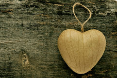 Heart-shaped ornament. A paperboard heart-shaped ornament on an old wooden surface with a copy space Royalty Free Stock Photos
