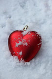 Heart shaped ornament in the snow Royalty Free Stock Photography