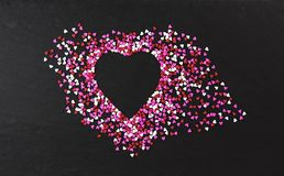 Heart shaped outline on black background. Heart shaped outline made of red, pink and white candy mini hearts on black slate background. Hearts fan out from stock image