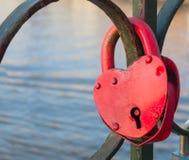 Heart shaped padloc. Aged rusty locked heart shaped padlock on metal railing royalty free stock photos