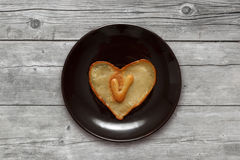 Heart shaped pancake with letter V inside on dark brown plate on wooden background Royalty Free Stock Photography