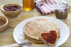 Heart shaped pancake with strawberry jam on stack of pancakes Stock Image