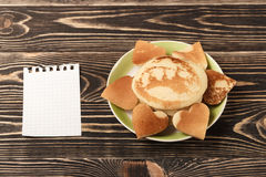 Heart-shaped pancakes with card on wooden table Royalty Free Stock Photo