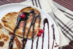 Heart shaped pancakes with chocolate and cranberries on porcelai Royalty Free Stock Photos