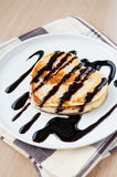 Heart shaped pancakes with chocolate on plate. Heart shaped pancakes with chocolate sauce on white porcelain plate. Closeup Royalty Free Stock Photo