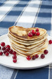 Heart shaped pancakes with cranberries. Heart shaped pancakes with cranberries on white  porcelain plate. Celebration dessert. Closeup Stock Images