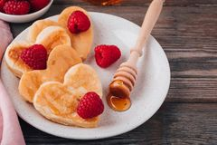 Heart shaped pancakes with raspberries and honey for St. Valentine`s Day royalty free stock image