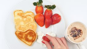 Heart-shaped pancakes with strawberry on a white dish. Simple breakfast for Valentine`s Day Royalty Free Stock Photo