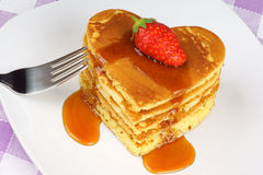 Heart-shaped pancakes with syrup and strawberry Royalty Free Stock Images