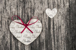 Heart shaped paper Christmas ornaments on a rustic wood background Stock Image
