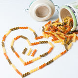 Heart-shaped pasta. Three colors fusilli raw pasta going out of the jar, forming heart shape photographed from above Stock Photo