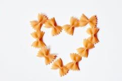 Heart shaped pasta. Farfalle on white background Stock Photos