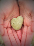 Heart-shaped pebble in a child's hands Royalty Free Stock Image