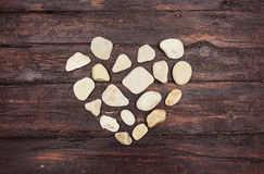A heart shaped pebble stones on a old wood Stock Photography