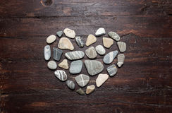 A heart shaped pebble stones on a old wood Stock Photos