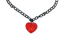 Heart Shaped Pendant and necklace. Heart shaped pendent, in red metal with red swaroski crstals and gothic black chain on white background Stock Photography