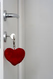Heart shaped pendant. Heart shaped plush pendant on key in lock of white door stock images